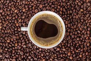 weiße Tasse Kaffee auf einem Haufen Kaffeebohnen.