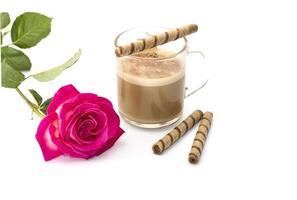 schöne scharlachrote Rose und Cappuccino mit röhrenförmigen Keksen foto