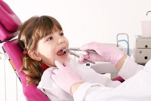 Zahnarzt extrahierte den Zahn kleines Mädchen mit einer Zange foto