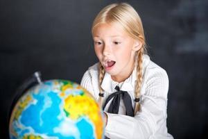 überraschtes Schulmädchen mit Globus foto