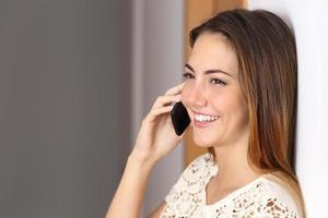 Frau, die auf dem Handy zu Hause oder im Büro spricht foto