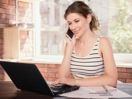 Geschäftsfrau, die an Laptop-Computer zu Hause arbeitet foto