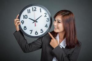 asiatische Geschäftsfrau zeigt auf eine Uhr und lächelt foto