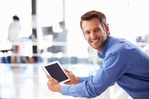 Porträt des Mannes im Büro unter Verwendung der Tablette, die zur Kamera lächelt foto