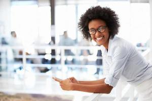 Porträt der lächelnden Frau im Büro, das auf Handy spricht foto