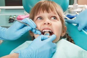 Nahaufnahme eines kleinen Mädchens, dessen Zähne von Unbekannten überprüft wurden foto