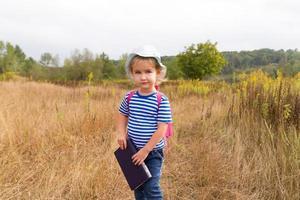 kleines Mädchen mit einem Rucksack und einem Buch foto