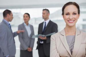 lächelnde Geschäftsfrau posiert, während Kollegen zusammen sprechen foto