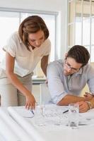 konzentrierte Kollegen, die im Büro an Bauplänen arbeiten foto