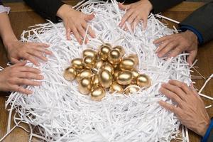 Kollegen um ein Nest aus goldenen Eiern foto