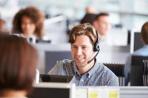 junger Mann arbeitet im Call Center, umgeben von Kollegen foto