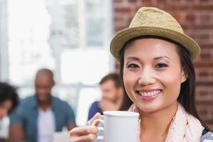 Frau, die Kaffeetasse mit Kollegen hinter im Büro hält foto