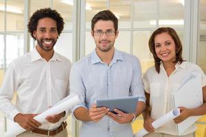 Geschäftskollegen mit Blaupausen und digitalem Tablet im Büro