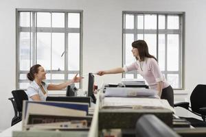 Geschäftsfrau, die Dokument an Kollegen über Schreibtisch im Büro weitergibt foto