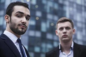 Porträt von zwei ernsten jungen Geschäftsleuten, die die Kamera betrachten foto