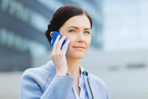 junge lächelnde Geschäftsfrau, die auf Smartphone anruft foto