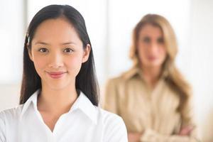 Porträt der mittleren erwachsenen Geschäftsfrau, die im Büro lächelt foto