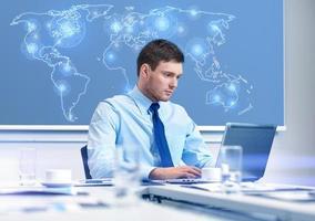 Geschäftsmann mit Laptop, der im Büro arbeitet foto