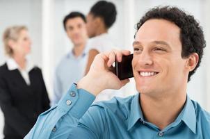 lächelnder Geschäftsmann, der auf Handy spricht foto