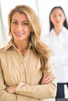 schöne Geschäftsfrau, die Arme im Büro verschränkt foto