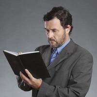 Geschäftsmann, der im Organisator gegen grauen Hintergrund schreibt foto