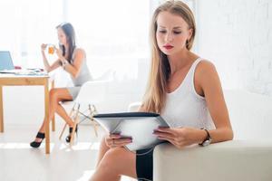Porträt der Geschäftsfrau mit Ordner, der im Büro auf sitzt