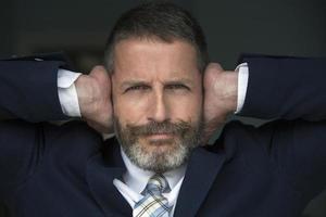 Porträt des gutaussehenden Geschäftsmannes, der seine Ohren bedeckt foto