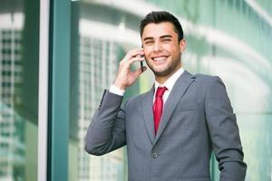 schöner Geschäftsmann, der am Telefon spricht foto