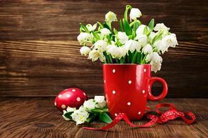 Schneeglöckchen in einem Tassenmuster und gemalte Eier foto