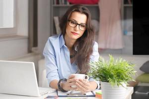 junge schöne Geschäftsfrau, die zu Hause arbeitet foto