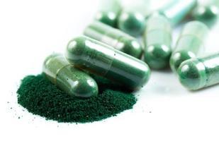 grüne Kräutermedizinkapsel lokalisiert auf weißem Hintergrund foto