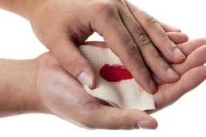 Person, die medizinischen Verband auf blutender Handfläche hält foto