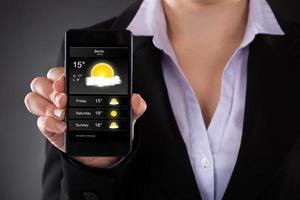 Geschäftsmann, der Wettervorhersage auf Handy zeigt foto