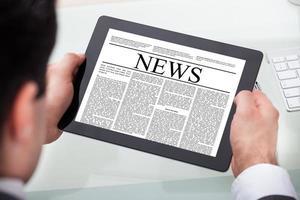 Geschäftsmann, der Nachrichten auf digitalem Tablett liest foto