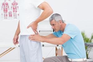 Arzt untersucht seinen Patienten zurück foto
