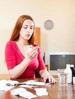 Frau, die Temperatur mit Thermometer zu Hause misst foto