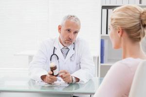 konzentrierter Arzt, der ein Rezept gibt foto