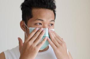 asiatischer Mann, der eine Gesichtsmaske trägt foto