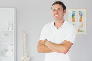 hübscher glücklicher Physiotherapeut, der mit verschränkten Armen steht foto