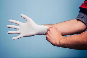 Mann, der chirurgischen Latexhandschuh anzieht foto