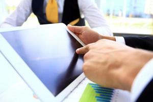 Unternehmer, der Finanzstatistiken analysiert, die auf dem Tablet-Bildschirm angezeigt werden foto