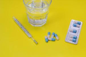 Wasserglas, Thermometer und Medikamente foto