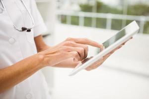 Nahaufnahme des Arztes unter Verwendung der digitalen Tablette in der Arztpraxis foto
