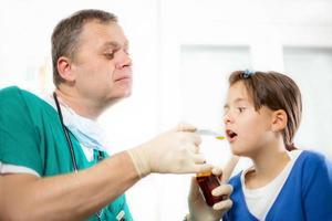 Kinderarzt, der einem kleinen Mädchen eine Medizin gibt foto