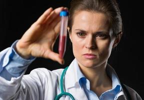 Ärztin, die auf Reagenzglas mit Blut schaut foto