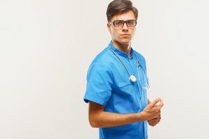 Arzt mit Stethoskop um den Hals vor grauem Hintergrund foto