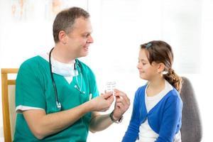 Arzt gibt Mädchen eine Pille foto