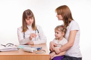 Kinderarzt schaut auf Thermometer und sitzt neben Frau