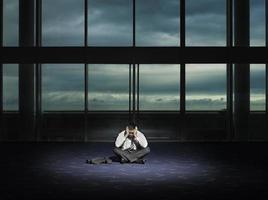 frustrierter Geschäftsmann im dunklen Raum foto