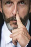 Porträt eines Mannes, der sich die Nase reibt foto